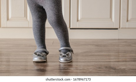 Close up little girl kid orthopedic shoes on wood floor. Space for text