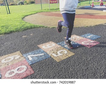 Close up of a little girl playing hopscotch at the park.