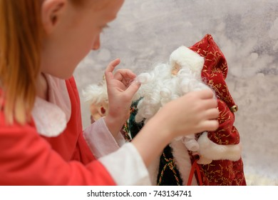 close up of little girl with Santa Claus costume on playing with Father Christmas ornament on a blurred winter background