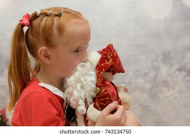 close up of little girl with Santa Claus costume on kissing a Father Christmas ornament on a blurred winter background