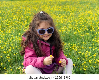 Close up of a little girl that gathering flowers sitting on a flowery meadow