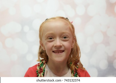 close up of little girl with tinsel and baubles draped around her neck on a blurred winter background