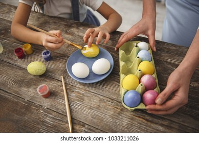 Close up of little hands painting eggs in yellow color. Mom is standing near