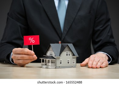 Close up of little house and hand keeping percent tablet. Concept of deal and real estate