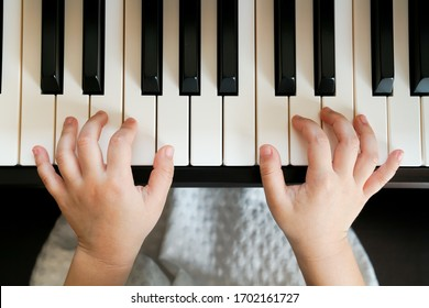 Close up of a little kid's hands is playing, learning and practicing the piano. Piano chords in the key of C major. Music abilities for kids. Hobby and activity for the children. Selective focus.