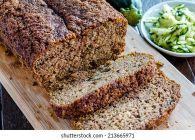 Close up of loaf of homemade zucchini bread sitting on wooden cutting board with fresh shredded zucchini