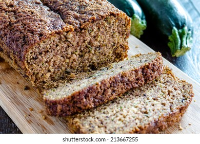 Close up of loaf of homemade zucchini bread sitting on wooden cutting board with fresh zucchini squash
