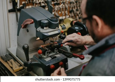 Close up of a locksmith while working with key duplicating machine