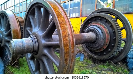 Close up of a locomotive wheels and gears in a train yard.