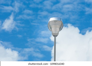 Close up lonely LED street lamp locate on walkway beside stree road with blue sky in the background. (Selective focus)