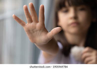 Close up lonely little girl offering stretching hand at camera, asking help, domestic violence victim, upset preschool child kid waiting for parents, adoption and children custody concept