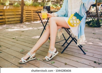 close up of long skinny legs of young attractive slim woman in cafe, street style, summer fashion trend, footwear, sandals, blue cape, white boho dress, fashionable accessories, sunny, perfect skin