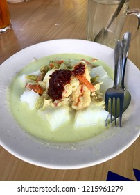 Close up of lontong-Traditional Indonesian and Malaysian food served on plate with fork and spoon captured with smartphone.