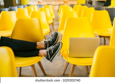 close up look at legs of young stylish woman sitting in lecture hall, laptop, classroom with many yellow chairs, student education online, freelancer, footwear, sneakers, shoes fashion trend