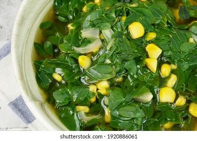 Close up look of Sayur Bening Daun kelor or Moringa Oleifera clear soup with Sweet Corn. Selected focus, full frame