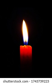 A close up look of a single red wax candle light up blue re fire at the middle position with total dark black isolated background for Christmas, Romantic Valentine's Day, Meditation macro portrait.