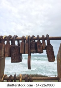 Close up of love / commitment padlocks on a fence by the sea.waves in the background. These locks are rusted closed.