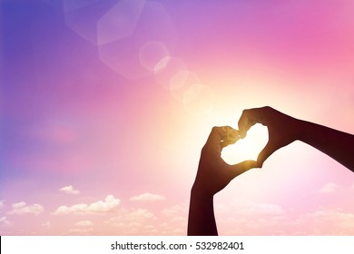Close up love shape of hand at sunset sky pink filter of pattern color tone.