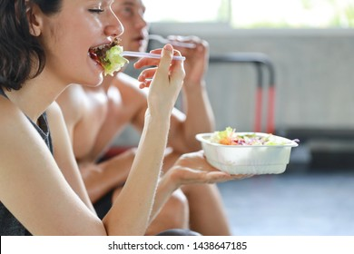 close up lovely caucasian couple fitness man and woman take a rest and eating salad in gym after finish fitness training with happy smiling face