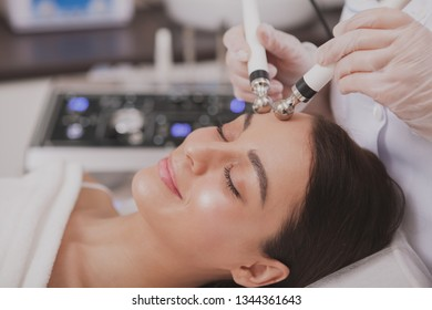 Close up of a lovely relaxed young woman enjoying facial microcurrent therapy by professional cosmetologist. Beautiful woman with perfect skin getting face care procedures by beautician