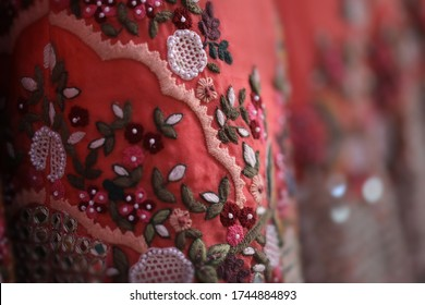 close up of lovely wedding skirt called lehenga, an Indian traditional wedding clothing in pink and red color with golden and crochet like flower embroidery in a blurred background