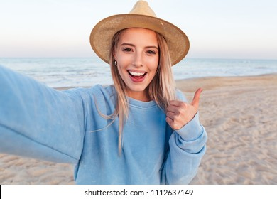 Close up of lovely young girl in summer hat taking a selfie and showing thumbs up gesture at the beach