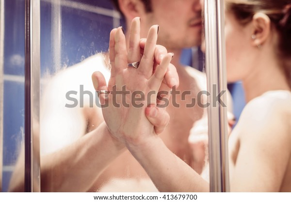 close up of a loving and caucasian couple's hands, while they are together in the shower - lifestyle and people concept