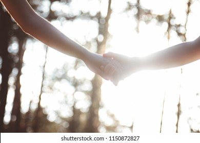Close up of loving couple holding hands. Friendship. Silhouette. Handshake. Helping hand. Overexposed.