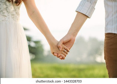 Close up of a loving couple holding hands in an intimate manner