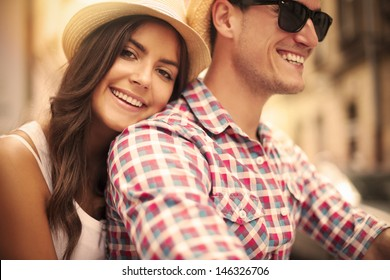 Close up of loving couple riding on bike in the city