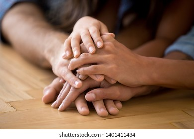 Close up of loving family stack hands on warm floor together show support and unity, caring parents join arms with child express devotion loyalty understanding. Bonding, good relationships concept