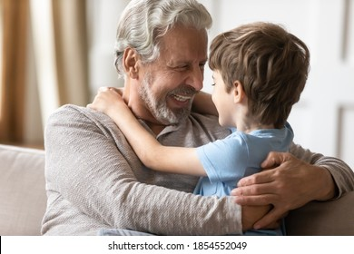 Close up loving grandfather and little grandson enjoying tender moment, sitting on couch at home, overjoyed smiling older man hugging adorable grandchild, having fun, two generation good relationship