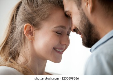 Close up of loving man and woman touching forehead having sweet tender moment together, happy millennial couple smile caressing each other, young husband and wife enjoy tenderness at home