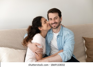 Close up loving wife kissing husband on cheek and hugging, young family enjoying tender moment, happy man looking at camera, embracing attractive woman girlfriend, sitting on cozy couch at home