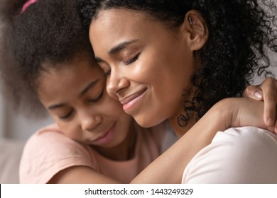 Close up of loving young african American mother hold little daughter in arms hugging caressing her at home, happy caring black mom having close intimate moment with preschooler girl kid making peace