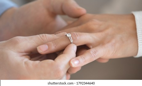 Close up loving young man putting engagement golden ring with diamond on bride finger, wedding proposal acceptance. Affectionate millennial couple in love decided getting married, marry me concept.