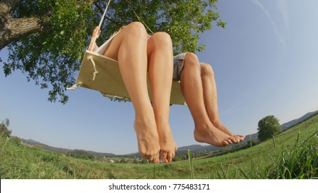 CLOSE UP LOW ANGLE: Barefoot man and woman swinging away from camera in tranquil natural scenery. Unrecognizable young couple having the time of their lives on rope swing in serene spring countryside.