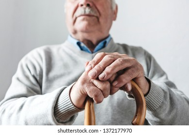 Close up low angle view of the crossed hands of an elderly man with mustache holding a walking cane in a concept of ageing and mobility