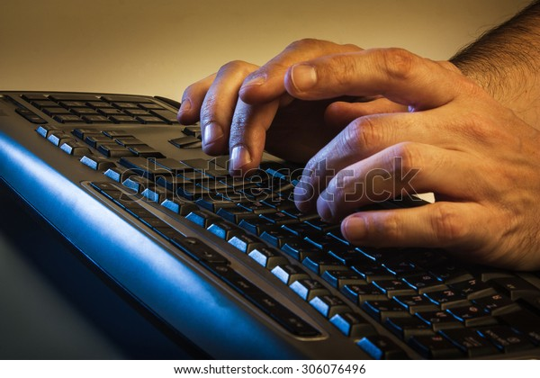 Close up low angle view of a man typing on a laptop computer in darkness conceptual