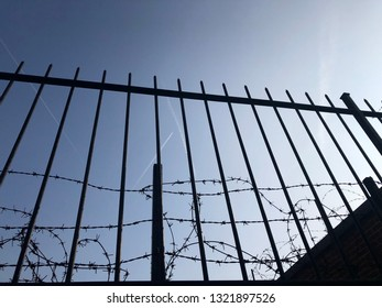 Close up low angle view of metal bars and barbed wire against clear blue sky