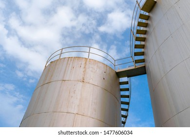 Close up low angle view of metallic grey cylindrical industrial oil and gas storage tanks with stairs along a road during daylight on a cloudy day.
