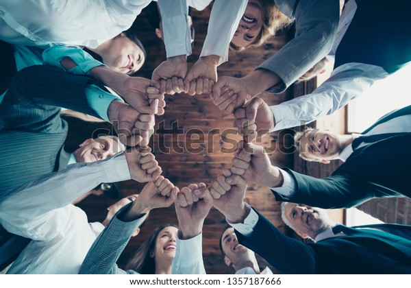 Cercano a los miembros de la foto de ángulo bajo miembros de negocios rodearla ella él sus manos los puños de los brazos juntos celebrar el premio del proyecto nominación poder inspiración vestida ropa ropa chaquetas formales pantalones