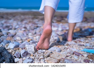 Close up low angle woman barefoot walking on beach with stone ground