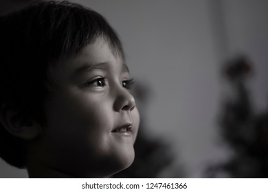 Close up low key lighting of happy kid face looking out with smile, Head shot low lighting of cute little boy smiling face, Dramatic side view in black and white monochrome portrait of positive child