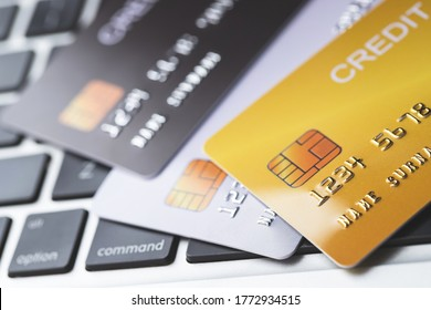 close up low key macro shot mock up credit card many stack of multicolored on a laptop computer keyboard for background. finance transaction or Transfer online pay money concept.
