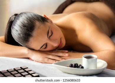 Close up low light portrait of young woman with eyes closed laying on couch in spa. Chocolate slab and hot cacao massage oil next to girl.
