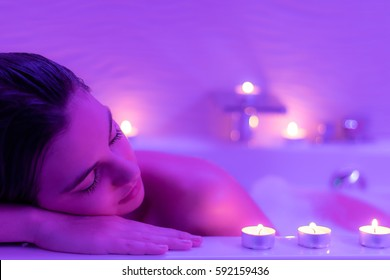 Close up Low light portrait of young woman relaxing in foam bath.Low colorful candlelight ambient with candles on bath tub.
