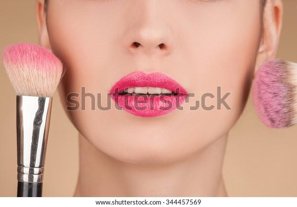若い女性の顔の下部の接写。彼女は頬に二本の筆で赤くなっている