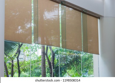Close up luxury Long blind, curtain, roller, shade, shutter protected sunlight with large glass wall and blur green tree background.