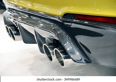 Close up of a luxury sportive car with four exhaust pipe and bumper realized in real carbon fiber.